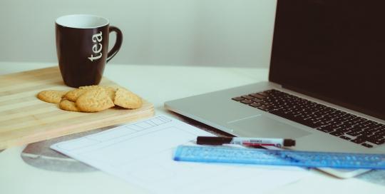 Kekse mit Teetasse und MacBook