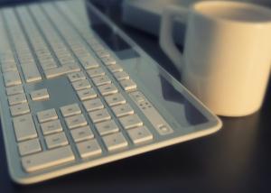 Tastatur und Kaffeetasse auf einer Schreibtischoberfläche.