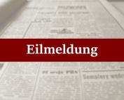 Schriftzug Eilmeldung vor unscharfer Zeitung