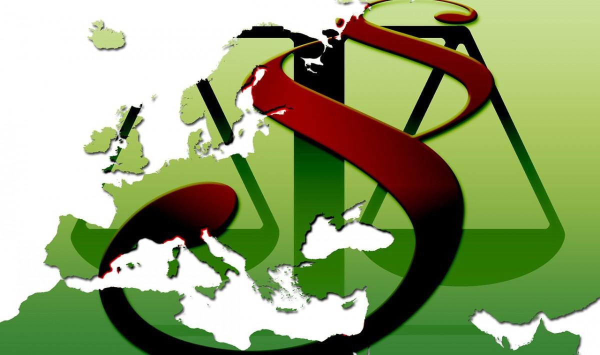 Grüne Europakarte mit Paragraphenzeichen und Waage.