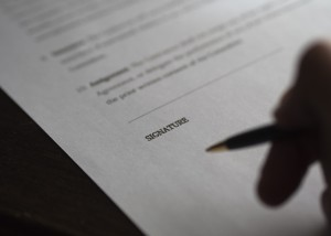 Vertrag mit schemenhafter Hand und Kuli bereit zur Unterschrift.